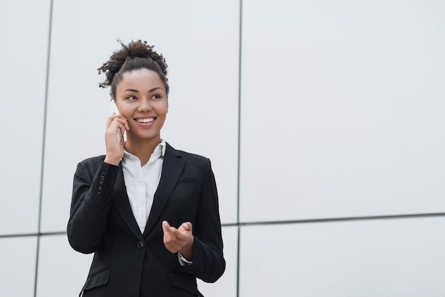 Gelukkige vrouw die op de telefoon spreekt Gratis Foto