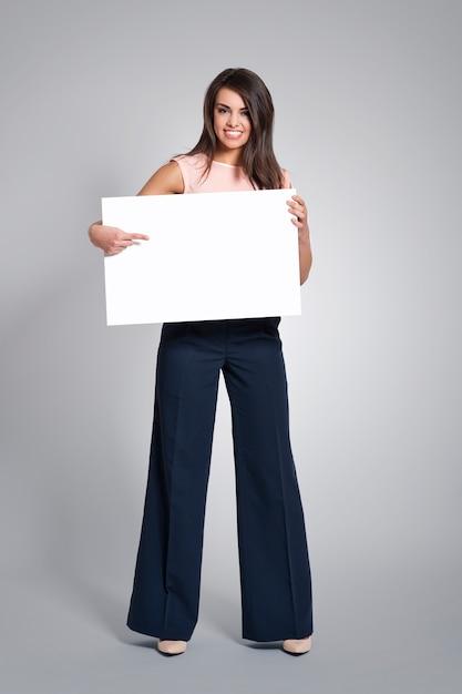 Gelukkige vrouw die op leeg whiteboard richt Gratis Foto