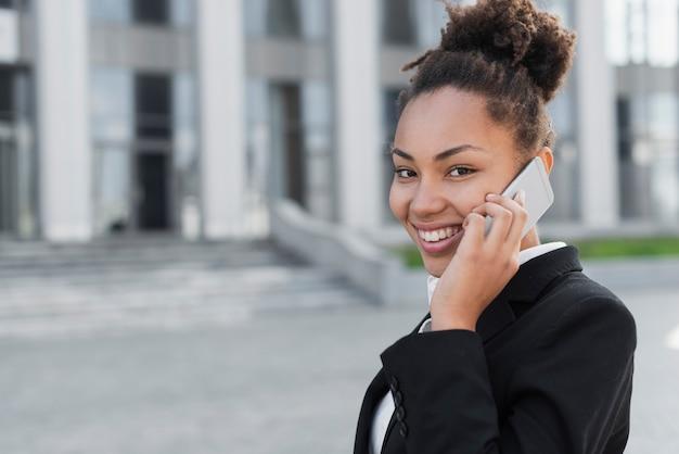 Gelukkige vrouw die op telefoon spreekt Gratis Foto