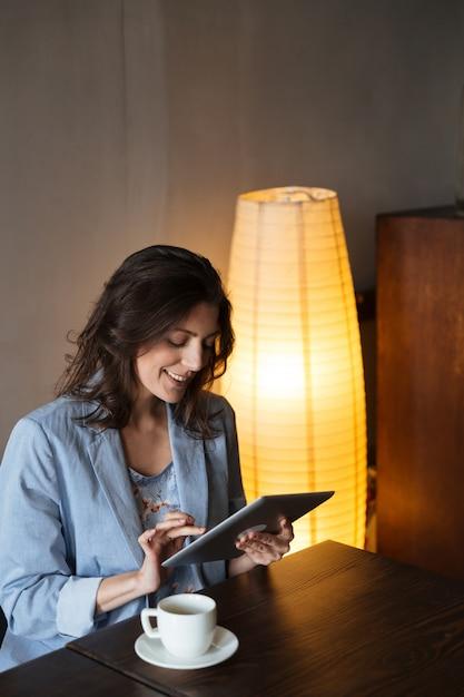 Gelukkige vrouw die tabletcomputer met behulp van. Gratis Foto