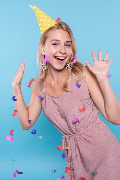 Gelukkige vrouw die terwijl confettien het vliegen stellen Gratis Foto