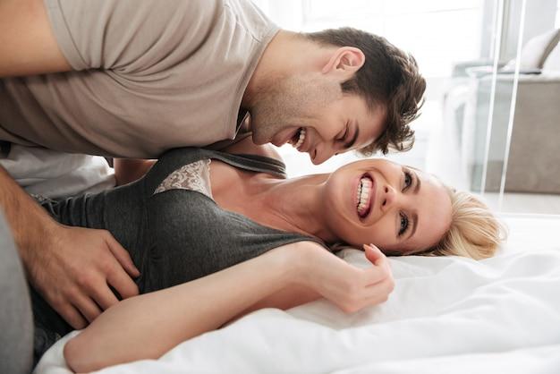 Gelukkige vrouw die terwijl het liggen en het spelen met haar echtgenoot glimlacht Gratis Foto
