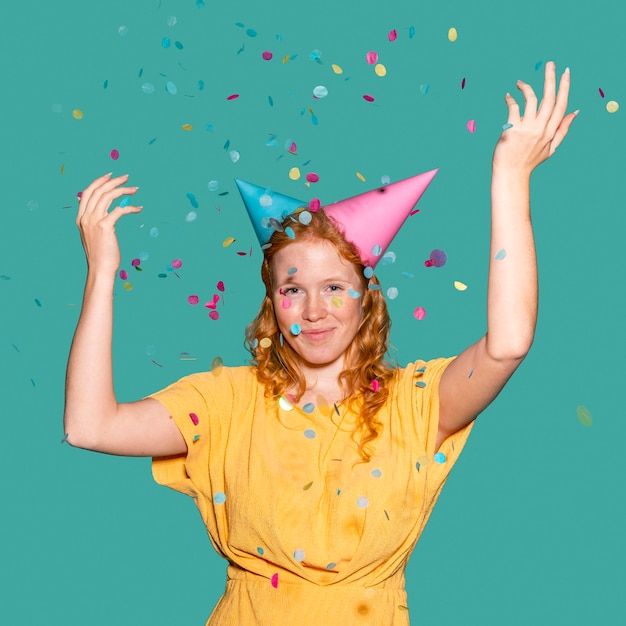 Gelukkige vrouw die twee verjaardagskegels draagt Gratis Foto