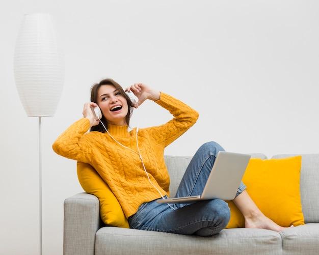Gelukkige vrouw die van haar muziek op hoofdtelefoons geniet Gratis Foto