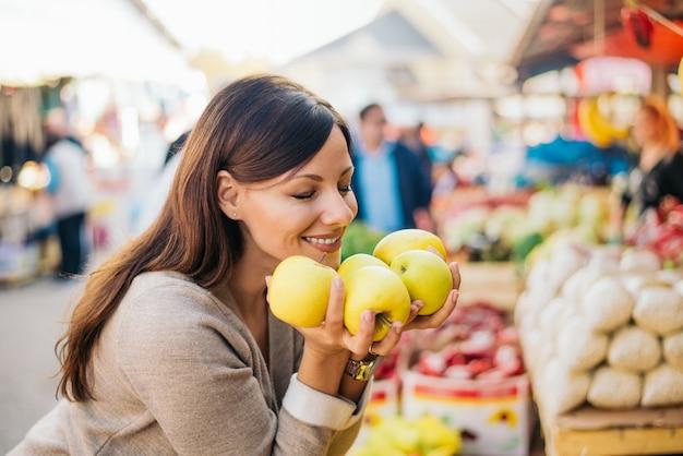 Gelukkige vrouw die van verse geur van paprika geniet bij markt. Premium Foto
