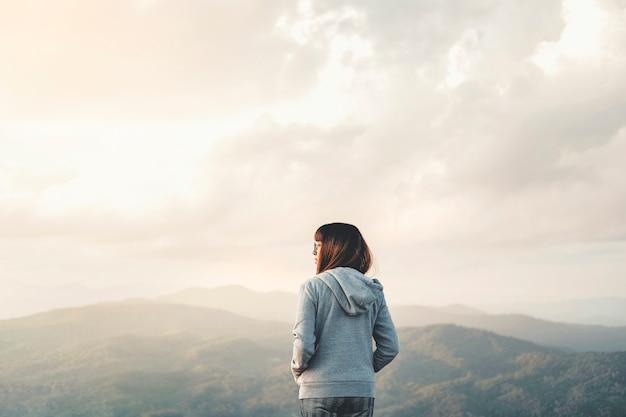 Gelukkige vrouw die van vrijheid bovenop berg met het concept van de zonsondergangontspanning genieten Premium Foto