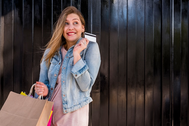 Gelukkige vrouw die zich met het winkelen zakken en creditcard bij muur bevindt Gratis Foto