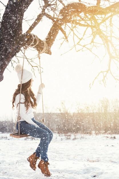 Gelukkige vrouw en kabelschommeling in de winterlandschap Premium Foto