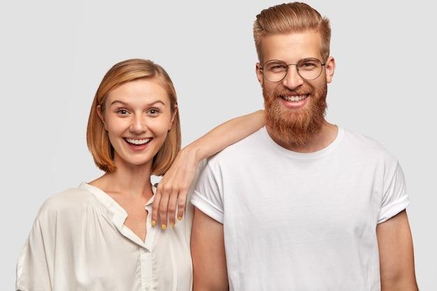 Gelukkige vrouw en man paar gekleed in casual witte kleding, hebben positieve uitdrukkingen Gratis Foto