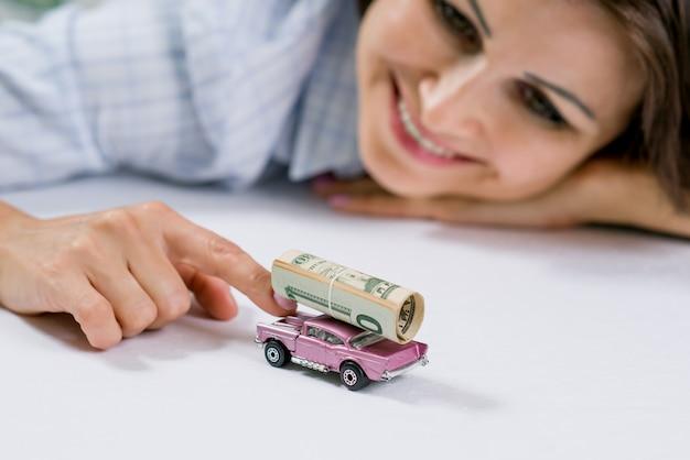 Gelukkige vrouw en speelgoedauto, geldbankbiljetten Premium Foto