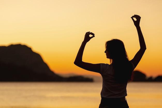 Gelukkige vrouw en zonsondergang op achtergrond Gratis Foto