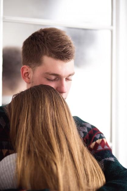Gelukkige vrouw gekleed in pullover legde haar hoofd op de schouder van de mens Premium Foto