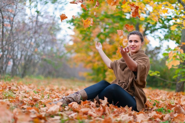 Gelukkige vrouw gooit herfstbladeren Gratis Foto
