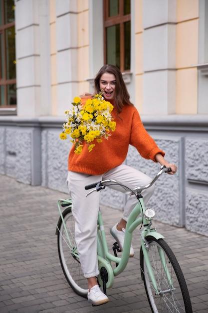 Gelukkige vrouw haar fiets buiten met bloemen Premium Foto