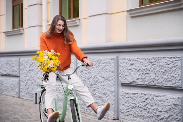 Gelukkige vrouw haar fiets buiten met boeket bloemen Premium Foto