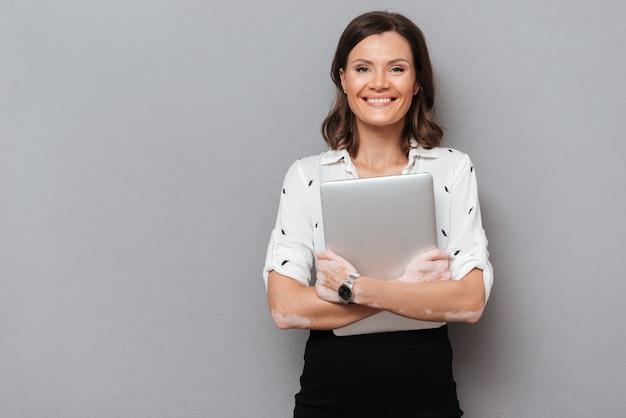 Gelukkige vrouw in bedrijfskleren die haar laptop computer koesteren en de camera op grijs bekijken Gratis Foto