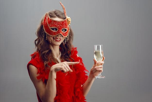 Gelukkige vrouw in een rood carnaval-masker en een boa met een opgeheven glas champagne Premium Foto