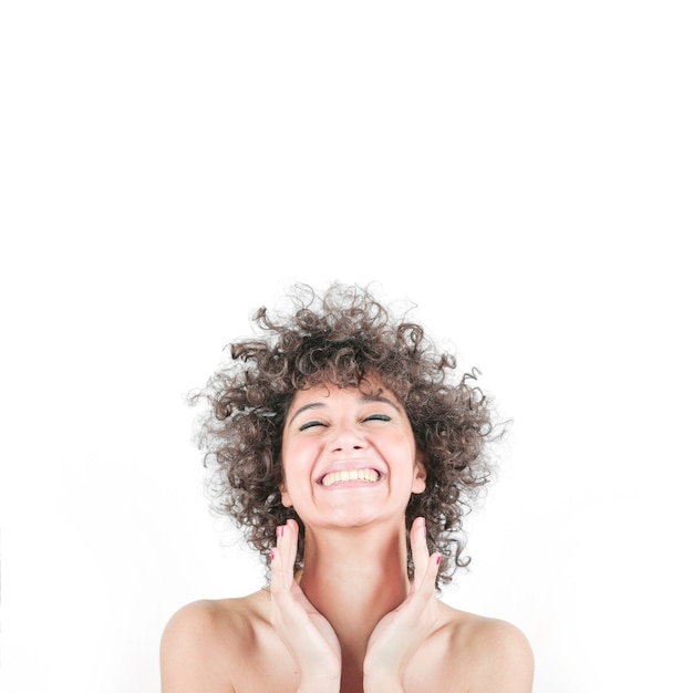 Gelukkige vrouw in krullend haar dat over witte achtergrond wordt geïsoleerd Gratis Foto