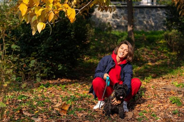 Gelukkige vrouw in park met herfstbladeren Gratis Foto