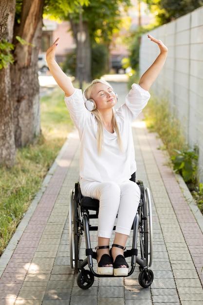 Gelukkige vrouw in rolstoel met hoofdtelefoons Gratis Foto
