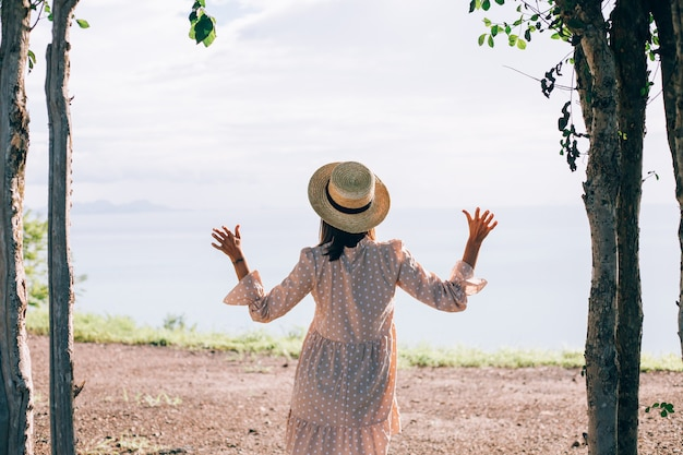 Gelukkige vrouw in schattige zomerjurk en strohoed op vakantie met tropische exotische uitzichten Gratis Foto