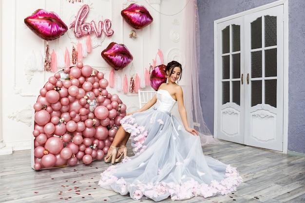 Gelukkige vrouw in tule jurk met roze ballons. luxe Premium Foto