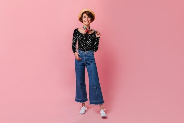 Gelukkige vrouw in vintage jeans die zich op roze muur bevindt Gratis Foto