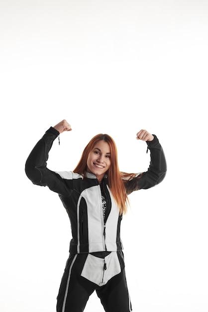 Gelukkige vrouw in zwart-witte beschermende motorkleding met omhoog handen Gratis Foto