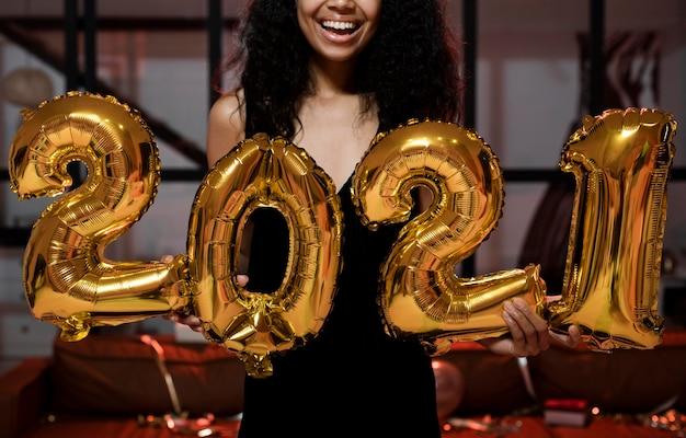 Gelukkige vrouw met 2021 ballonnen op feestje Gratis Foto