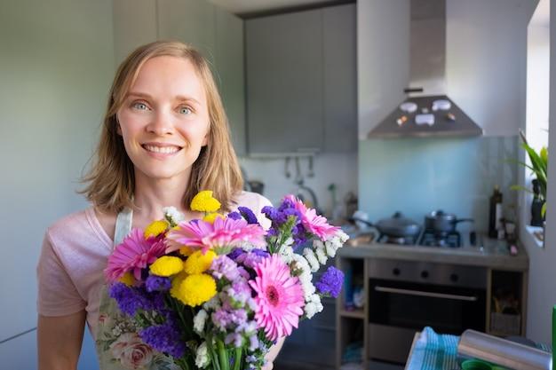 Gelukkige vrouw met bos bloemen, poseren in huis keuken, camera kijken en glimlachen. vrouwendag of speciaal datumconcept Gratis Foto