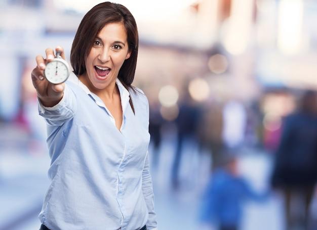 Gelukkige vrouw met een klok in haar hand Gratis Foto