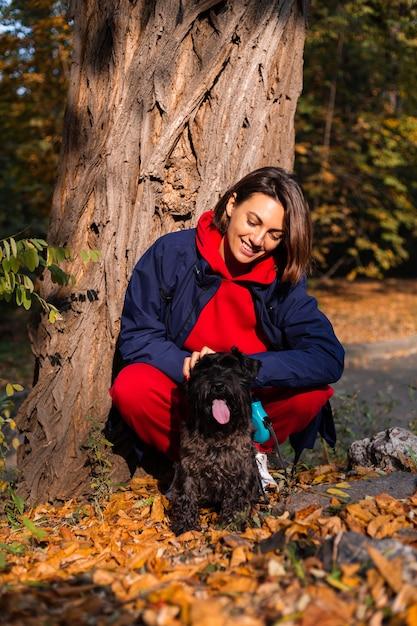 Gelukkige vrouw met hond in park met herfstbladeren Gratis Foto