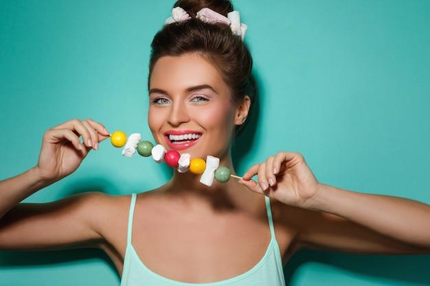 Gelukkige vrouw met kleurrijke make-up en zoet suikergoed op vleespen Premium Foto