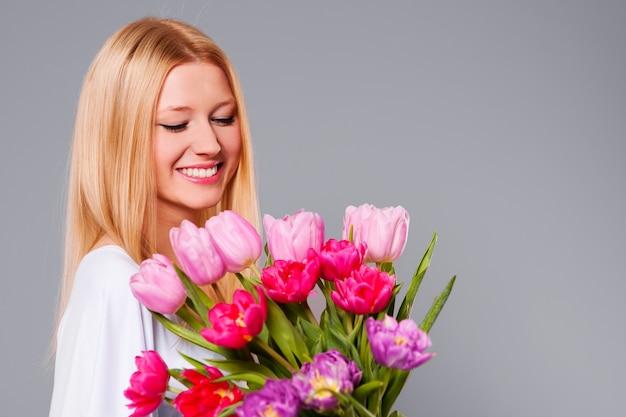 Gelukkige vrouw met roze en paarse tulpen Gratis Foto