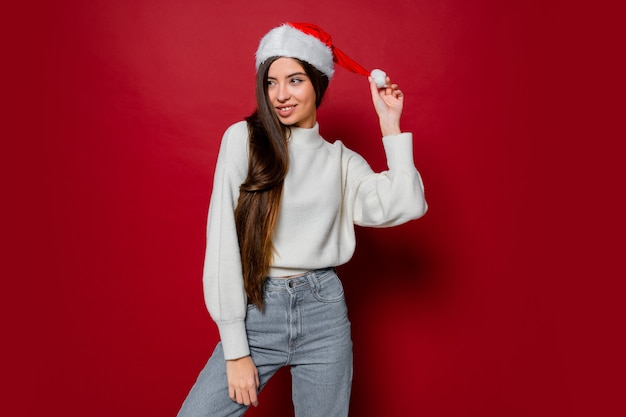 Gelukkige vrouw met verbazingwekkende lange haren in kerstmuts poseren Gratis Foto