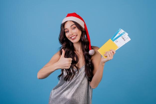 Gelukkige vrouw met vliegtickets en paspoort dat kerstmishoed draagt die over blauw wordt geïsoleerd Premium Foto