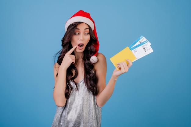 Gelukkige vrouw met vliegtickets en paspoort dragen kerstmuts Premium Foto