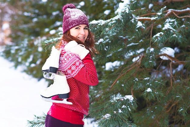 Gelukkige vrouw met winter skates op haar schouder. winteractiviteiten en sport. Premium Foto