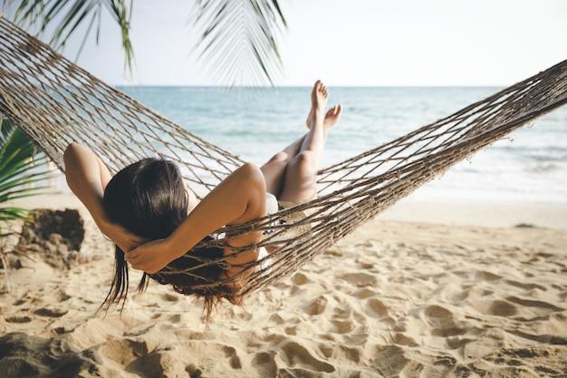 Gelukkige vrouw ontspannen in een hangmat Premium Foto