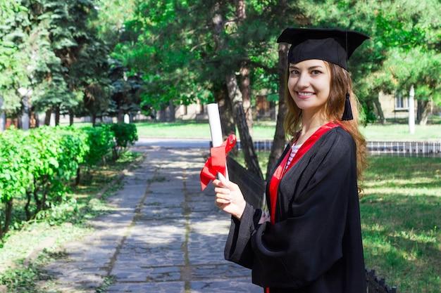 Gelukkige vrouw op haar graduatiedag. universiteit, onderwijs en gelukkige mensen Premium Foto