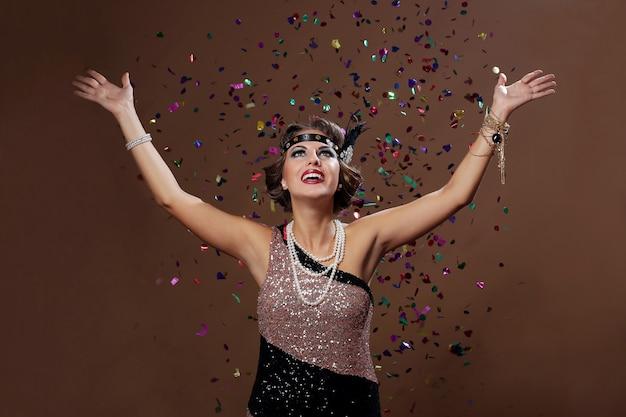Gelukkige vrouw opzoeken met confetti achtergrond Gratis Foto