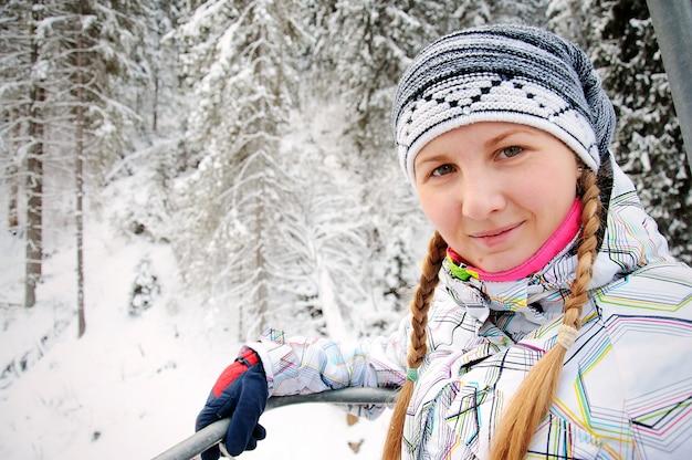 Gelukkige vrouw stijgt op de lift in de karpaten. detailopname. winter natuur. er valt zware sneeuw. twee vlechten op het hoofd. Premium Foto