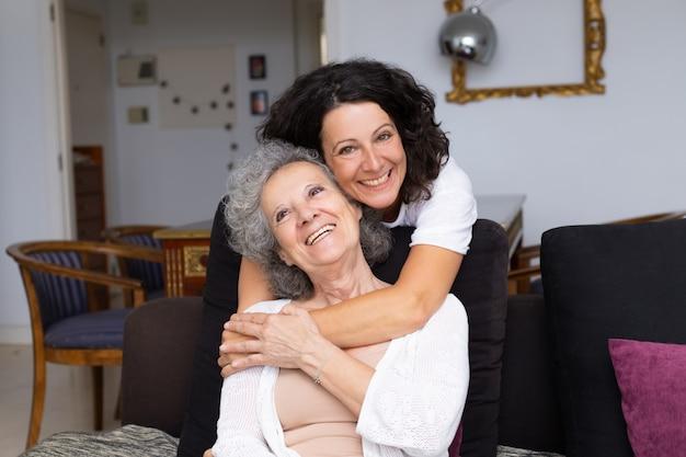 Gelukkige vrouw van middelbare leeftijd knuffelen senior dame Gratis Foto