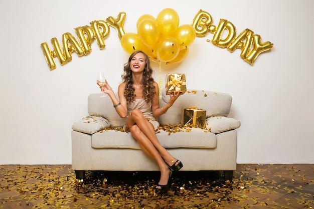 Gelukkige vrouw viert verjaardag in gouden confetti zittend op de bank Gratis Foto
