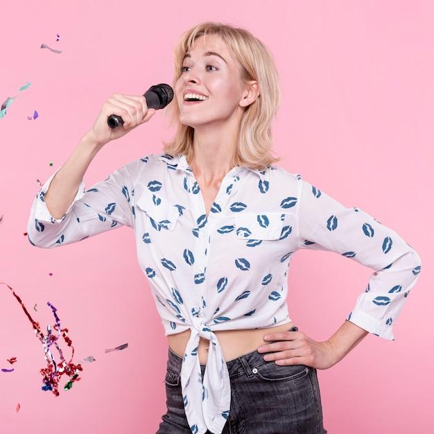 Gelukkige vrouw zingen karaoke op feestje Gratis Foto