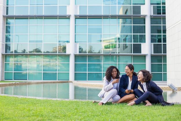 Gelukkige vrouwelijke bedrijfscollega's die van het werkonderbreking genieten Gratis Foto