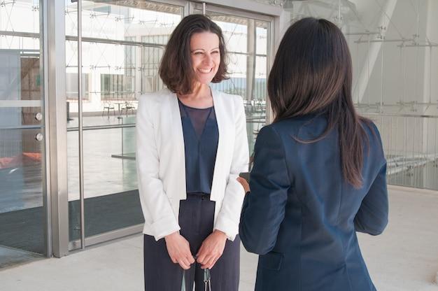 Gelukkige vrouwelijke collega's die in bureauzaal spreken Gratis Foto