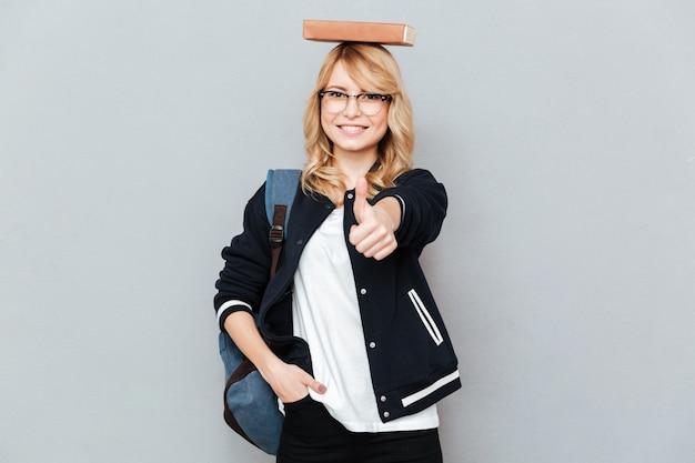 Gelukkige vrouwelijke nerd in grappige oogglazen met boek op hoofd die duim tonen Gratis Foto