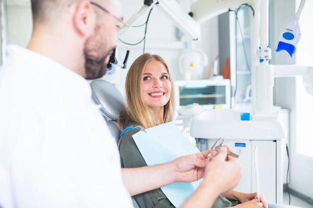 Gelukkige vrouwelijke patiënt die tandarts bekijken die plastic tandenmodel met vernierbeugel meten Gratis Foto