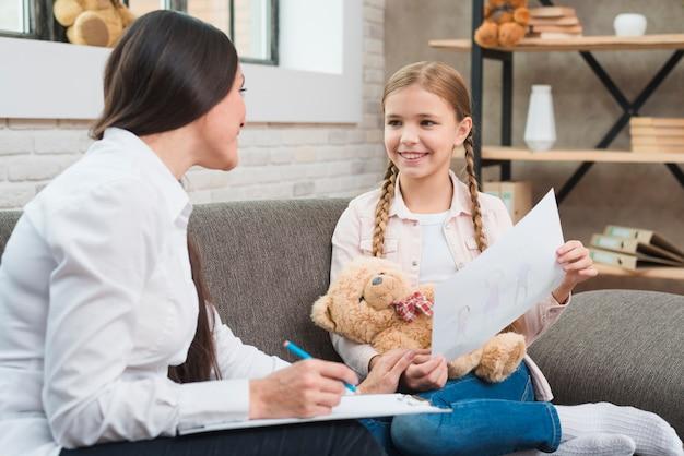 Gelukkige vrouwelijke psycholoog die met een meisje spreekt en nota op papier maakt Gratis Foto
